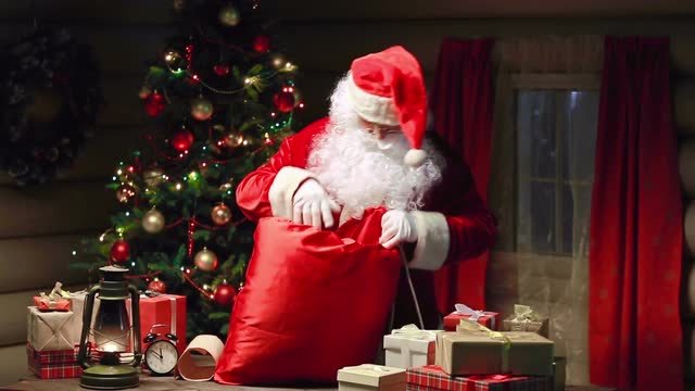 santa-claus-packing-gift-boxes-in-sack-and-waving-hand_vk-7tcpgm__m0000